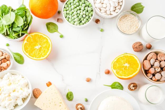 Concepto de comida saludable. conjunto de alimentos ricos en calcio - productos lácteos y veganos ca marco de fondo de mármol blanco