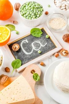Concepto de comida saludable. conjunto de alimentos ricos en calcio: productos lácteos y veganos de ca, superficie de mármol blanco