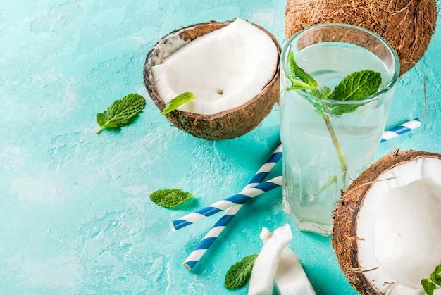 Concepto de comida sana agua de coco orgánica fresca con cubitos de hielo de coco y menta sobre fondo azul claro