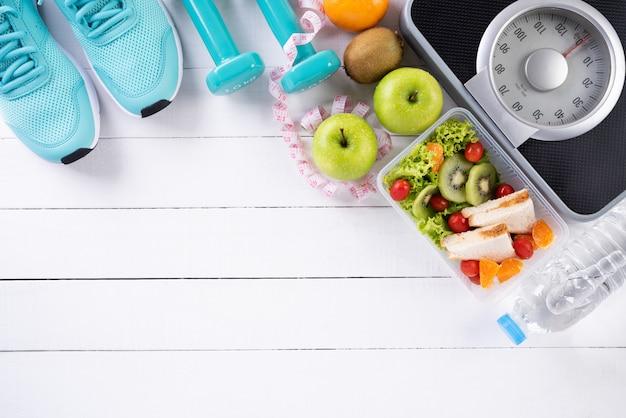 Concepto de comida sana y deporte sobre fondo blanco de madera.