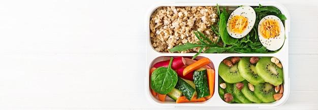 Concepto de comida sana y estilo de vida deportivo. almuerzo vegetariano desayuno saludable. nutrición apropiada. caja de almuerzo. bandera. vista superior. endecha plana.