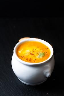 Concepto de comida sana mezcla caliente sopa de verduras y queso mozzarella en taza de cerámica blanca