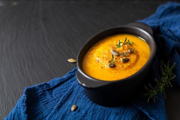 Concepto de comida sana mezcla caliente de sopa de verduras y semillas de calabaza en taza de cerámica negra