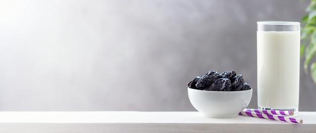 Concepto de comida sana, vegetarianismo, dieta. vaso de yogur y ciruelas pasas. fondo brillante con espacio de copia.