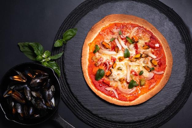 Concepto de comida tortilla casera pizza de mariscos en placa de piedra pizarra negra