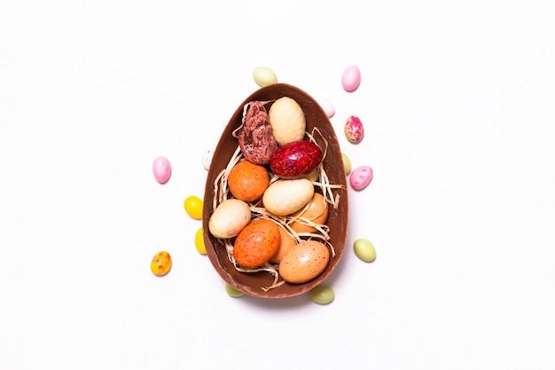 Concepto de comida de vacaciones coloridos dulces y chocolate huevos de pascua en el fondo blanco