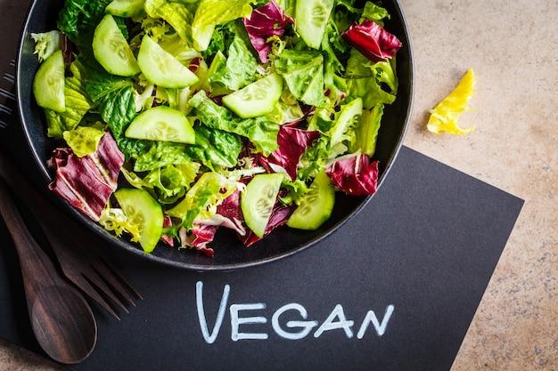 Concepto de comida vegana. ensalada de vegetales verdes en placa negra y cuaderno con la palabra vegana, vista superior.