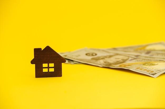 Concepto de compra de casa. hipoteca legal. manguera con dinero sobre la mesa amarilla.