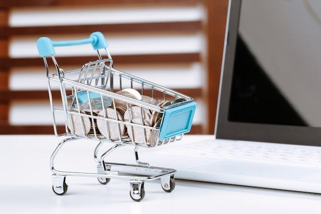 Concepto de compra en línea. carro de compras, laptop en el escritorio