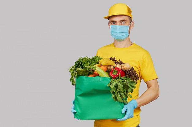 Concepto de compra en línea. mensajero masculino en uniforme amarillo, máscara protectora y guantes con una caja de supermercado con frutas y verduras frescas. entrega a domicilio de alimentos durante el coronavirus en cuarentena