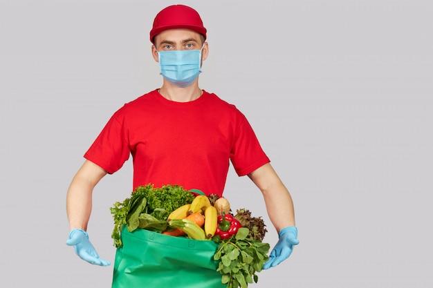 Concepto de compra en línea. mensajero masculino en uniforme rojo, máscara protectora y guantes con una caja de supermercado con frutas y verduras frescas. entrega a domicilio de alimentos durante el coronavirus en cuarentena