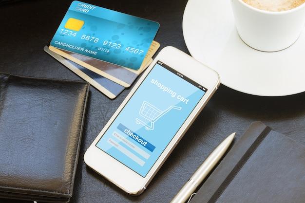 Concepto de compra móvil: tienda virtual en la pantalla del teléfono con tarjetas de crédito y billetera