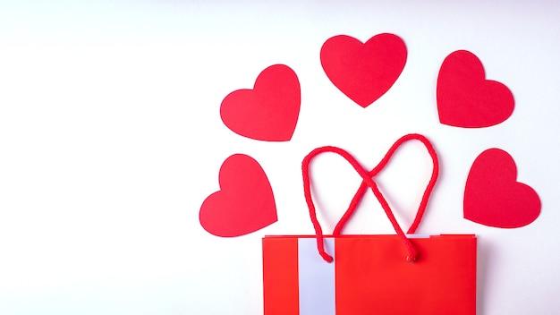 Concepto de compra online. bolsa de regalo roja y corazones de papel rojo aislado en blanco