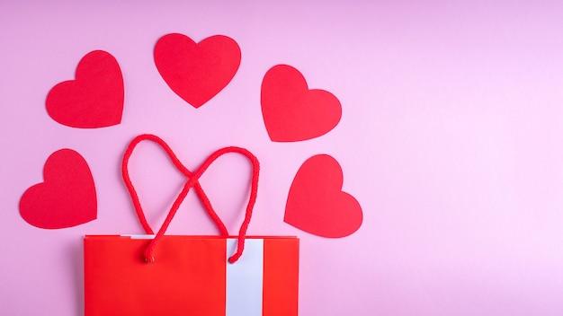 Concepto de compra online. bolsa de regalo roja y corazones de papel rojo sobre fondo rosa.