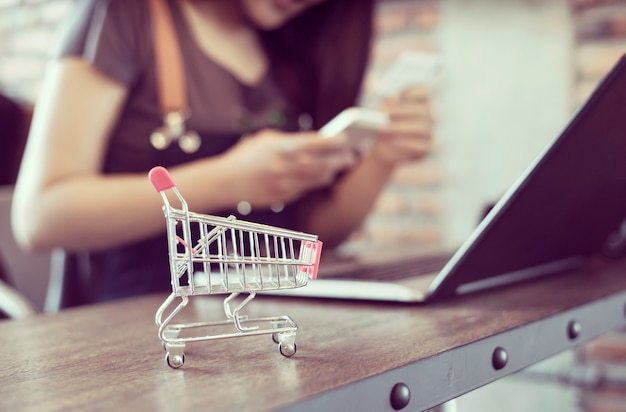 Concepto de compra online. carro de compras con manos sosteniendo tarjeta de crédito y usando laptop