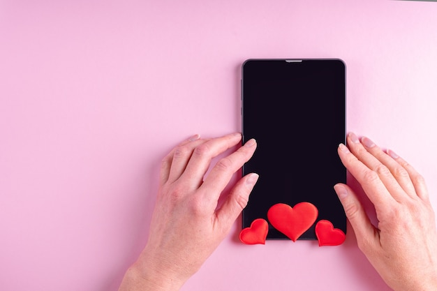 Concepto de compra online. manos femeninas en una pantalla de tableta en blanco negro con forma de corazón rojo