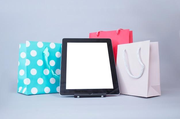 Concepto de compra online. maqueta de tableta de primer plano con pantalla blanca con bolsas de regalo brillantes en la pared gris.