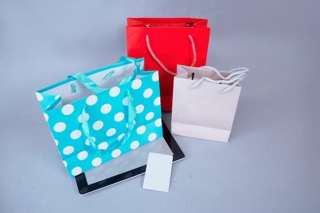 Concepto de compra online. maqueta de tableta de primer plano con pantalla en blanco y tarjeta de crédito en el contexto de bolsas de regalo brillantes.