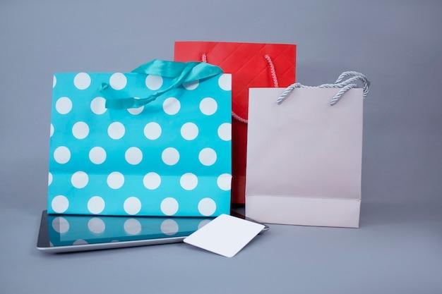 Concepto de compra online. maqueta de tableta de primer plano con pantalla en blanco y tarjeta de crédito contra la pared de bolsas de regalo brillantes.
