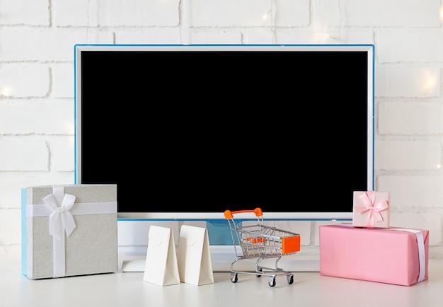 Concepto de compra online. monitor de computadora y regalos y compras para navidad.