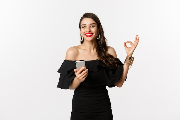 Concepto de compra online. mujer en vestido negro de moda, maquillaje, mostrando aprobación de signo bien y usando la aplicación de teléfono móvil, fondo blanco.