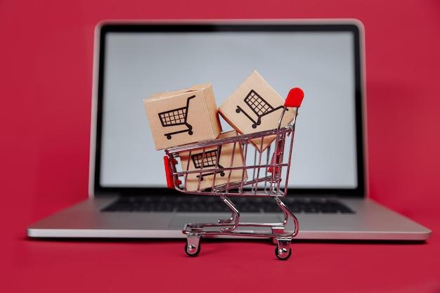 Concepto de compra online. ordenador portátil con mini carrito y cajas.