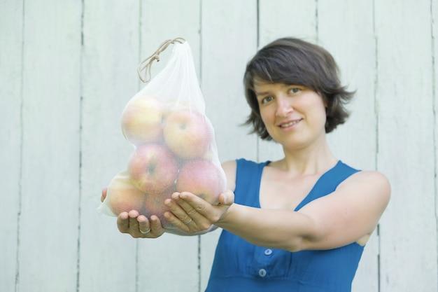 Concepto de compra de residuos cero. no de plástico de un solo uso. mujer sonriente que sostiene la bolsa de productos de malla reciclada reutilizable con manzanas orgánicas frescas
