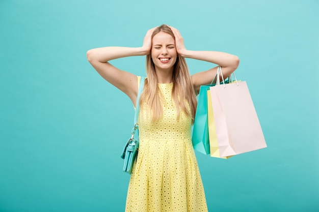 Concepto de compra y venta: hermosa joven infeliz en vestido amarillo elegante con bolsa de compras.