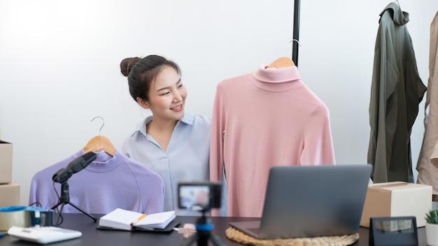 Concepto de compra en vivo una cámara digital que graba un video de una vendedora y se conecta con un dispositivo para transmitir una compra en vivo.