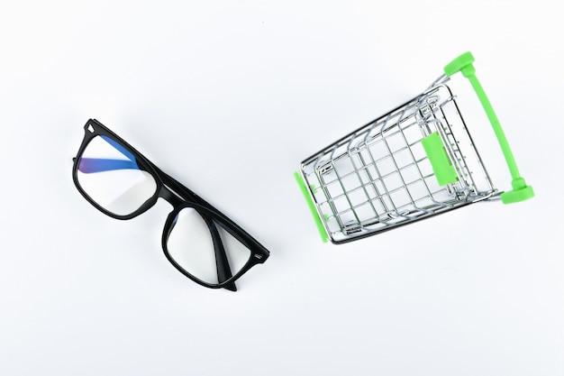 Concepto de compras de anteojos. concepto de compra en línea. carro y vasos en blanco
