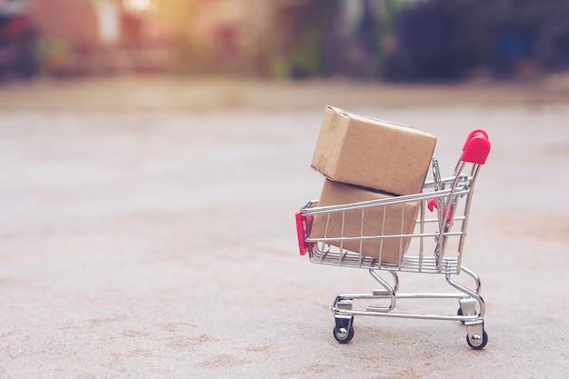 Concepto de compras: cajas de cartón o papel en el carrito de la compra en un piso de concreto. con copia sp
