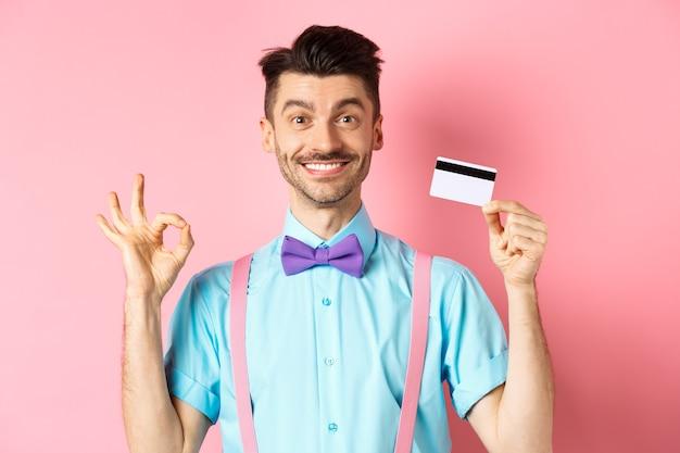 Concepto de compras. comprador masculino guapo sonriente que muestra el signo de ok y tarjeta de crédito plástica, comprando algo, de pie satisfecho sobre fondo rosa.