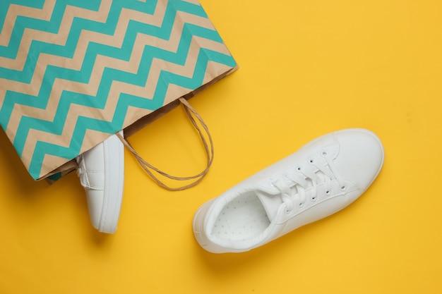 Concepto de compras estudio de moda disparo zapatillas blancas en bolsa de papel para ir de compras