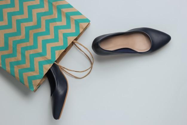 Concepto de compras foto de estudio de moda zapatos de tacón alto para mujer y bolsa de papel para ir de compras
