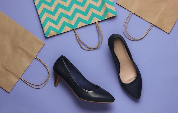 Concepto de compras foto de estudio de moda zapatos de tacón alto de mujer y bolsas de papel para ir de compras