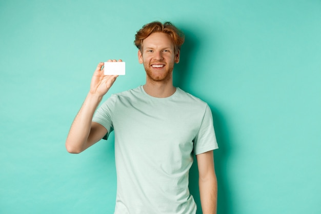 Concepto de compras. hombre guapo pelirrojo en camiseta mostrando tarjeta de crédito plástica y sonriendo, de pie sobre fondo turquesa.