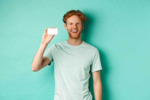 Concepto de compras. joven alegre en camiseta mostrando tarjeta de crédito de plástico y sonriendo, de pie sobre fondo de menta.