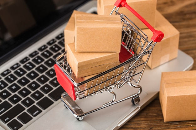 Concepto de compras en línea en casa cartones en un carrito de compras en un teclado portátil
