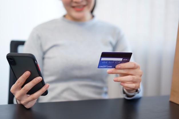 Concepto de compras en línea una compradora disfruta eligiendo y comprando productos en una tienda en línea.