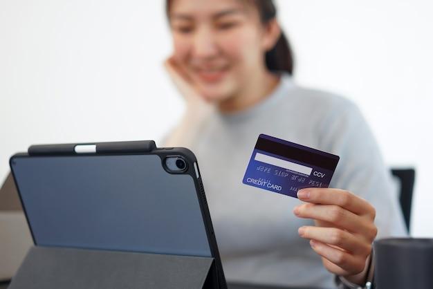 Concepto de compras en línea una mujer joven que usa su tarjeta de crédito para facilitar una compra en línea en la aplicación de compras en línea.