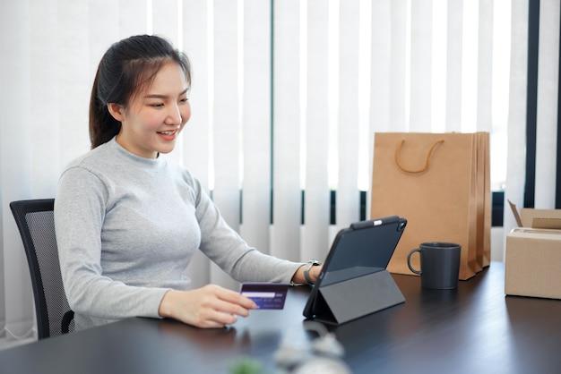 Concepto de compras en línea una mujer joven con su tarjeta de crédito para facilitar