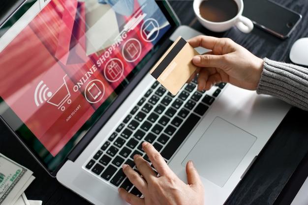 Concepto de compras en línea. mujer con tarjeta de crédito oro en la mano y compras en línea