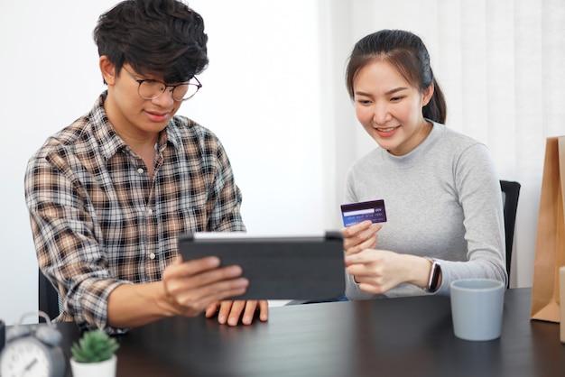 Concepto de compras en línea una pareja encantadora que agrega información de tarjeta de crédito para usar en transacciones financieras en línea.