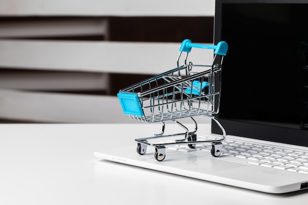 Concepto de compras en línea. pequeño carrito de juguete y gadgets sobre la mesa