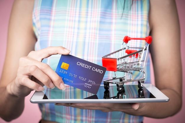 Concepto de compras en línea primer de la mano que sostiene la tarjeta de crédito con el carro en la pantalla de la tableta.
