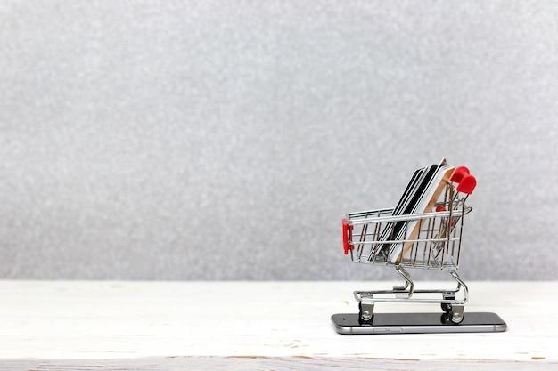 Concepto de compras en línea teléfono móvil o teléfono inteligente con carrito y tarjetas de crédito.