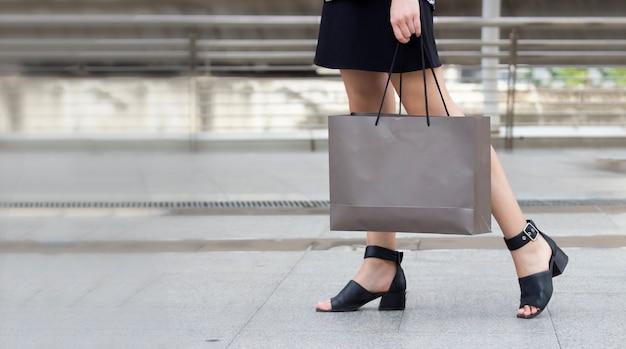 Concepto de compras; la mano de la mujer de negocios está sosteniendo bolsas de compras en una mano en el centro comercial después del trabajo