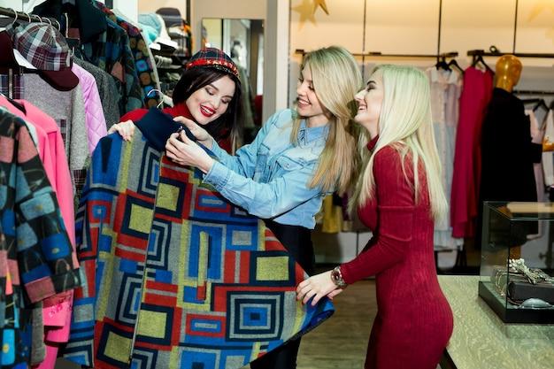 Concepto de compras, moda y amistad - tres amigos sonrientes probándose algo de ropa en el centro comercial.