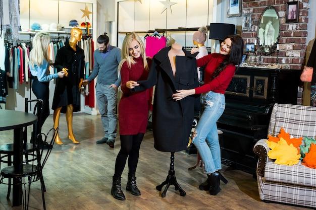 Concepto de compras, moda, ropa, estilo y personas: amigos felices probándose un abrigo en un centro comercial o una tienda de ropa