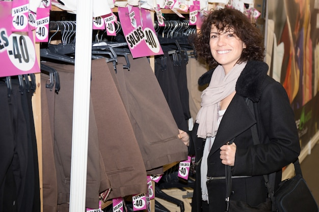 Concepto de compras - mujer eligiendo pantalones durante las compras en la tienda de ropa